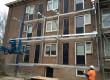 De doorgestorte balkons zijn afgezaagd en er is een stalen frame opgehangen aan de resterende betonrand in de gevel.