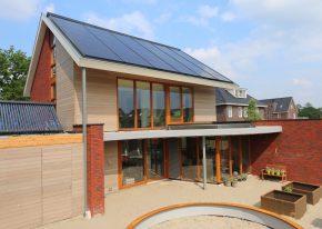 Het volvlakse PV-dak op de zuidzijde was bepalend in het ontwerp van de woning. Een overstek dient als zonwering. In de achtergevel is tevens het verdiepingshoge rooster van de zomernachtventilatie te zien