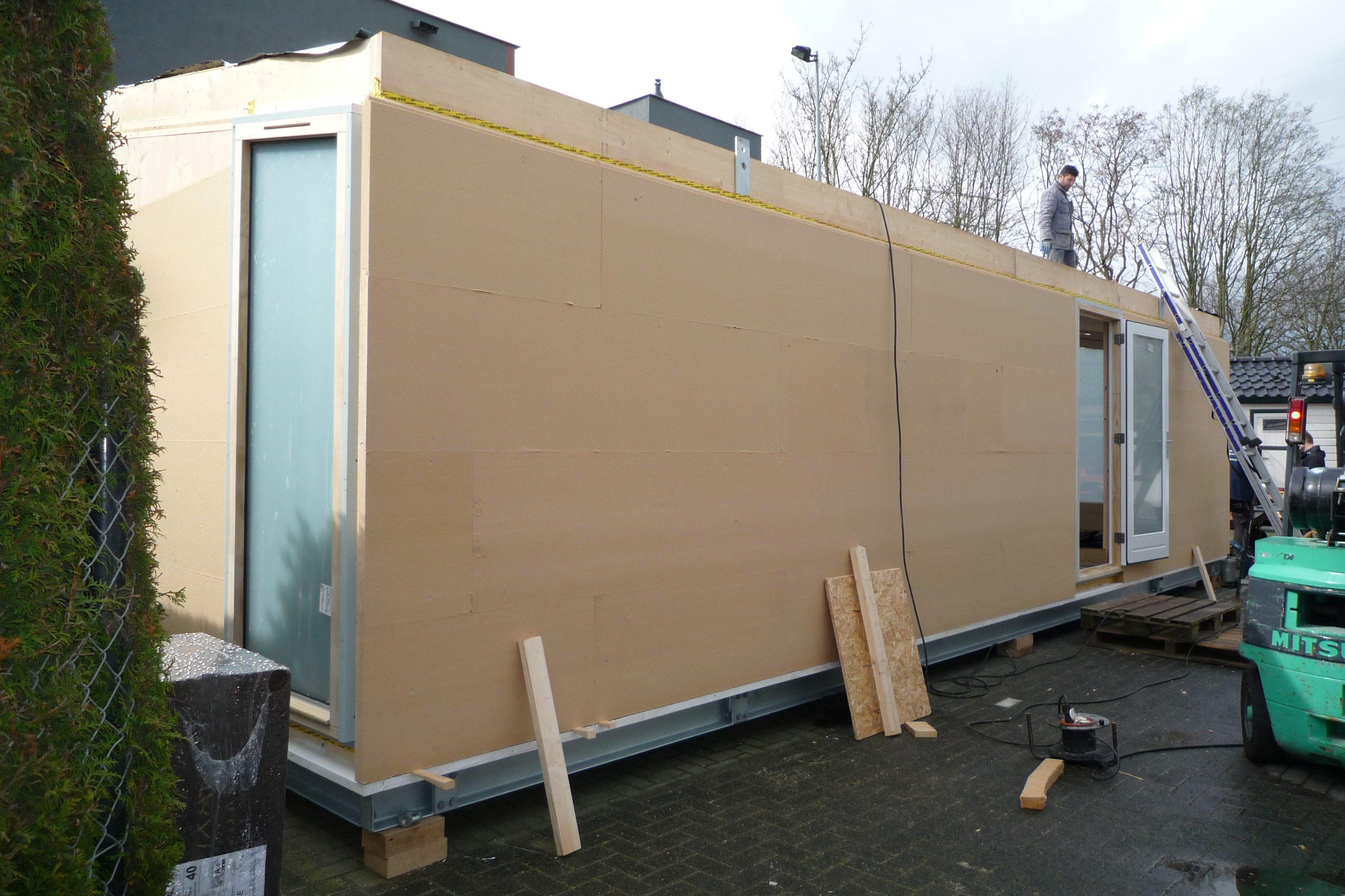 Na de montage van de geprefabriceerde massiefhouten vloer en wanden op de stalen fundering wordt de module geïsoleerd met houtvezelplaten.