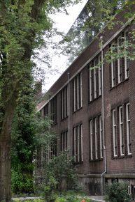 Door de weerspiegeling van lucht en bomen in de glazen gevels lijkt de dakopbouw als het ware op te lossen.