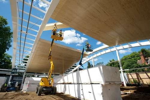 Slanke houtconstructie onder een gewelfd groen dak