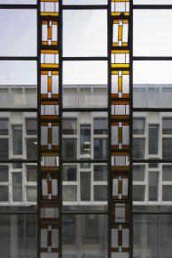 Het ontwerp van de composiet gevel is afgeleid van een bestaande gevel in het gebouw (voorgrond).