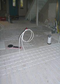 De vloerverwarming met PCM in de woonruimte is een droog systeem. In de badkamer ligt een nat systeem zonder PCM.