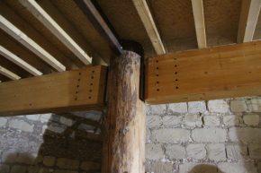 De gelamineerde liggers zijn opgehangen middels aan de boomstammen geschroefde T-platen.