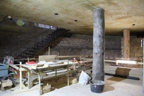 Een stalen sokkel met stekeinden verbindt de boomstamkolommen met de betonnen vloeren van de hoogste verdiepingen.