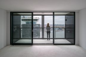 Geëmailleerde glazen gevels langs het balkon spiegelen het beeld, zodat het lijkt alsof het balkon doorloopt.