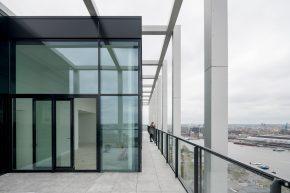 De aluminium gevelkolommen eindigen bij de penthouses in een open kroon