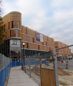 Met golvende lijnen en een houten gevelbekleding is de parkeergarage zorgvuldig in het landschap geïntegreerd