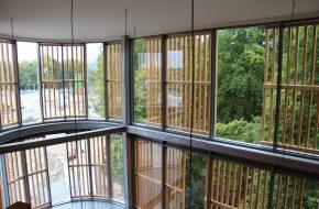 De houten gevelbekleding is deels doorgezet in het entreegebouw