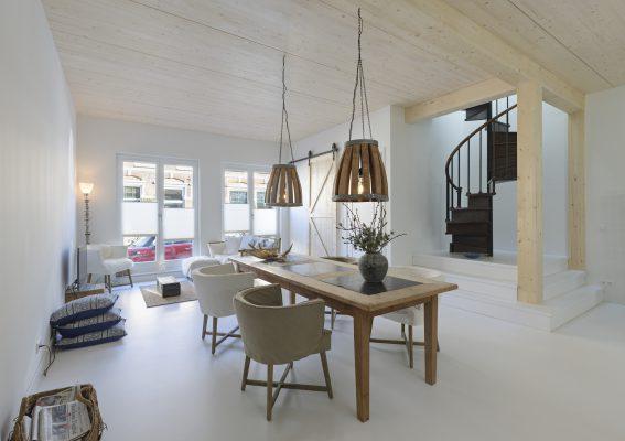 Houten vloeren en houten balken rondom de raveling voor het trapgat geven het interieur een warme uitstraling