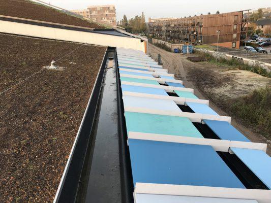 Bij het zwembad loopt de gevelbekleding aan drie zijden door tot op het dak. De elementen op het dak zijn niet geperforeerd. Onder de onderbreking in de beplating ligt een (tweede) goot
