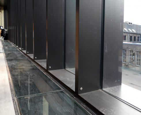 Beloopbare glasstroken markeren de verdiepingshoge puien in het nieuwe middendeel