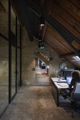 De glazen binnenwand voor het kantoor sluit aan tegen het originele dakbeschot van het bruggebouw