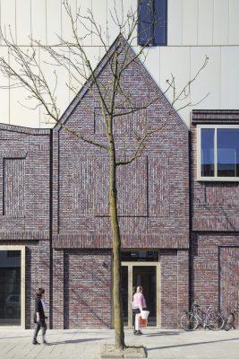 De gevelvlakken zijn opgedeeld in kleinere segmenten middels met steenstrips beplakte betonlateien en verticale dilataties.