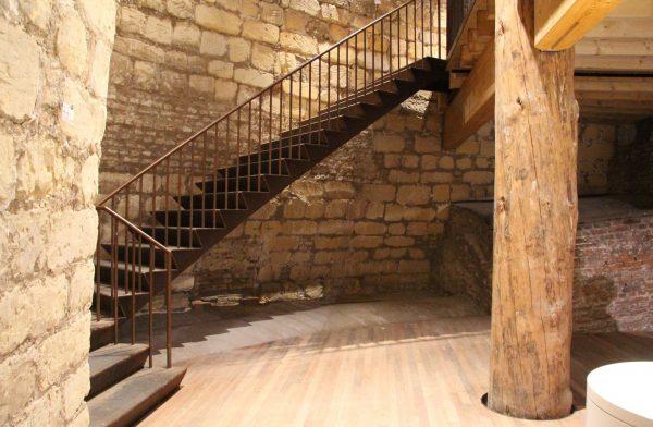 De houten vloer wordt gedragen door douglas stammen en sluit aan op de historische kanonsgang. Een geroeste stalen trap langs de gevel is deel van de tweede ontsluitingsroute.
