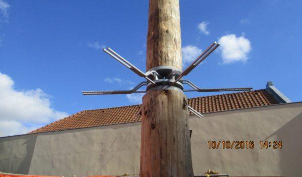 De boomstammen voor de bovenste bouwlaag zijn doorgestapeld. Een stalen krans met stekeinden is de verbinding met de betonvloer.