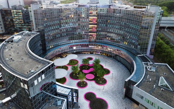 Zicht op het vernieuwde plein met de rvs-pergola's en de roze kunststof zitelementen rondom bomen en fonteinen