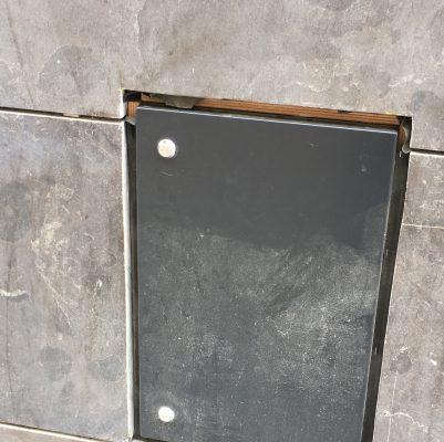 Niet van het kastje naar de muur, maar een kastje in de muur. En dat tussen eengevelbeplating, die ruim teruggehouden is. De houten omtimmering om het kastje is niet meer dan wat multiplex. Elke afwerking van de kopse kant ontbreekt zichtbaar