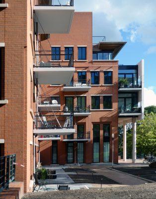 Door het gebruik van lichte materialen konden de balkons aan de bestaande constructie worden opgehangen