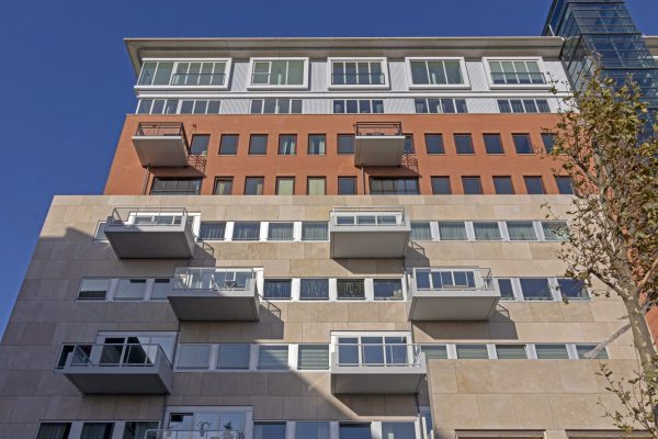 De balkons tegen de natuursteengevel bestaan uit composiet over een houten basisconstructie op stalen dragers