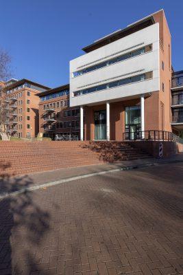 De bouwblokken staan op een verhoogd plein met eronder een parkeergarage