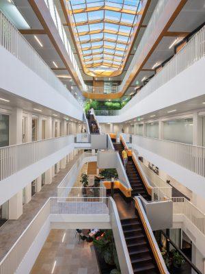 Het atrium in het hart van het gebouw is voorzien van een houten lichtstraat. Links is de oude buitengevel te zien die nu binnengevel is.