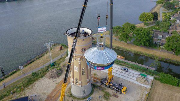 Met twee mobiele kranen wordt de nieuwe kroon op de watertoren geplaatst