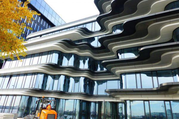 Links van de entree aan de voorzijde verspringen de golvingen in de glasgevels; rechts van de entree staan de glasgevels met inspringingen strak boven elkaar.