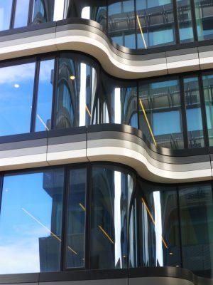 De krommingen in de glasgevels in de achtergevel staan niet recht boven elkaar. Dat komt door de verbreding van de inspringing in de gevel per verdieping.