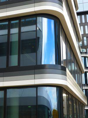 Detailopname van een hoek van het gebouw, waarop het gebogen glas en de vier gekleurde gevelbanden goed te zien zijn.