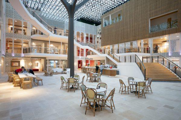 Het bladerdak loopt door in het centrale atrium op de vroegere binnenplaats van het carrévormige kantoor. Rondom zijn de atriumwanden voorzien van geperforeerde panelen met Arabische en bloemmotieven. Fotografie: Jasper Juinen