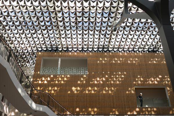 De aluminium bladeren hangen aan een railsysteem en zijn gevouwen in zeven varianten, waarbij de openingshoek varieert van open tot meer dicht. Fotografie: Jasper Juinen