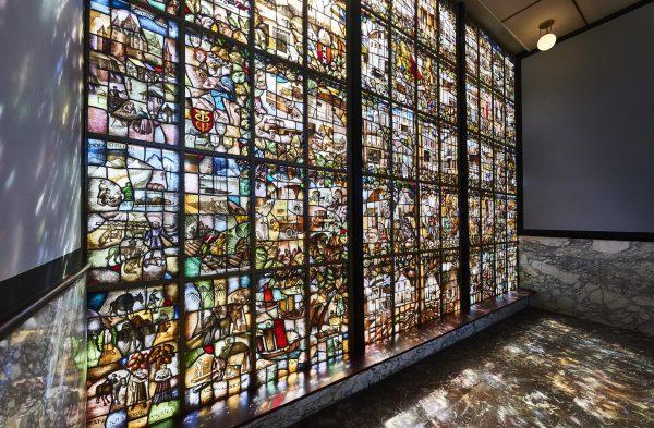 Zestig panelen in het glasinloodraam in de centrale hal verbeelden het leven en bedrijf van Jongerius