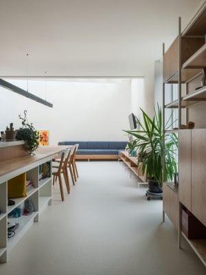 In de nieuwe ruimte is een walnoothouten keuken neergezet. In het midden staat een kookeiland dat tegelijkertijd eettafel is. De in warm eiken afgewerkte tafel is het hard van de ruimte.