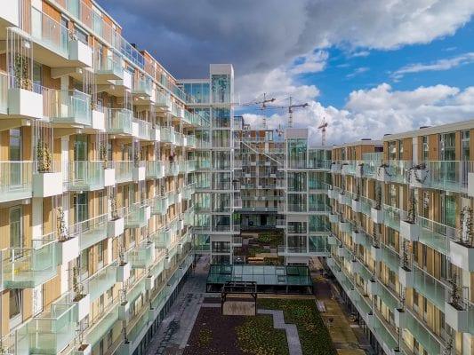 De appartementen grenzen aan een binnentuin op de tafelconstructie van de nieuwbouw.