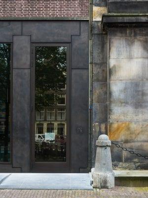 De bronzen gevelpanelen sluiten door de imperfecties, nuanceverschillen en het verouderingsproces van het materiaal naadloos aan op het karakter van de vervuilde gevel van het Trippenhuis.