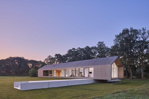De schuurwoning heeft een langgerekt volume van één bouwlaag met een kap, waarin het woonhuis, een carport en bijgebouw zijn ondergebracht.