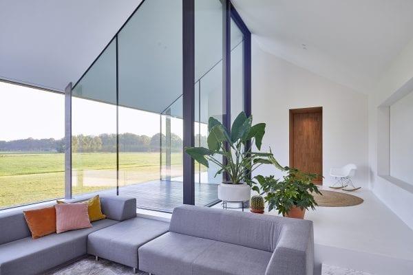 Het woonhuis heeft een open plattegrond met witte vloeren, wanden en plafonds. De woonkamer aan de noordzijde heeft een verdiepte zithoek met en een glazen patio met een dito schuifdeur van 4,5 meter hoog.