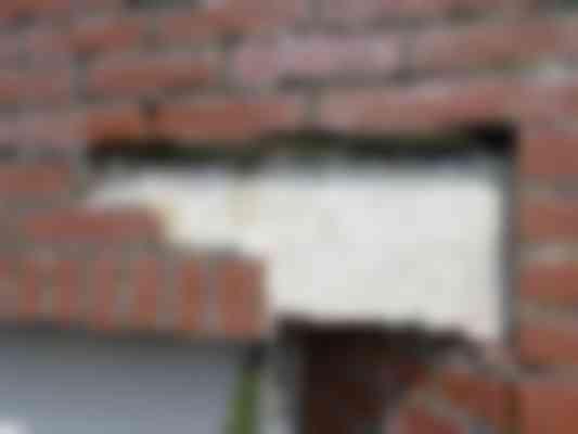 Na verwijdering van de steenstrips wordt de prefab betonlatei zichtbaar die een glad oppervlak heeft. De nog aanwezige lijmmortel vertoont degradatie